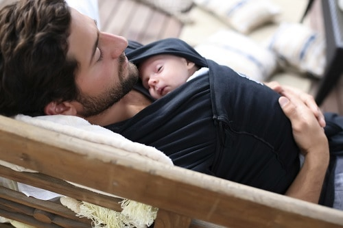 Man lying and baby wrap