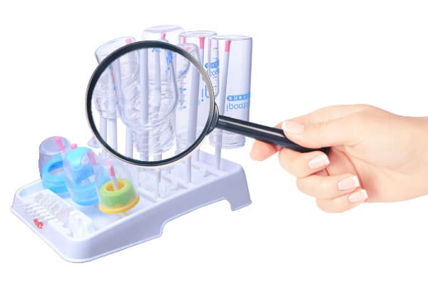 taking a closer look at a baby bottle drying rack with a magnifying glass