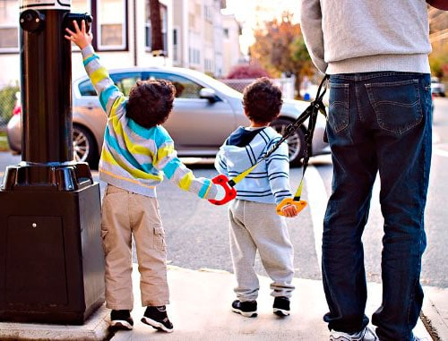 two children holding a walking handle on a busy street