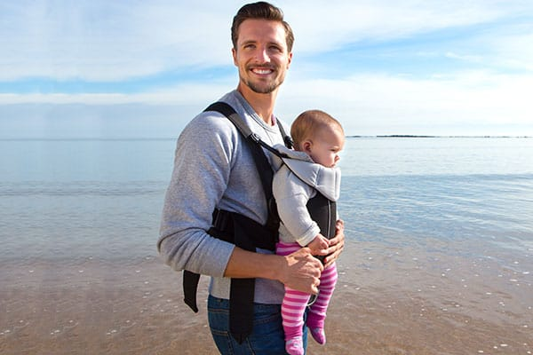baby being carried by dad in a soft structured baby carrier
