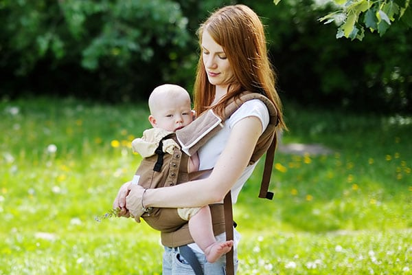 baby being carried by mom in soft structured baby carrier
