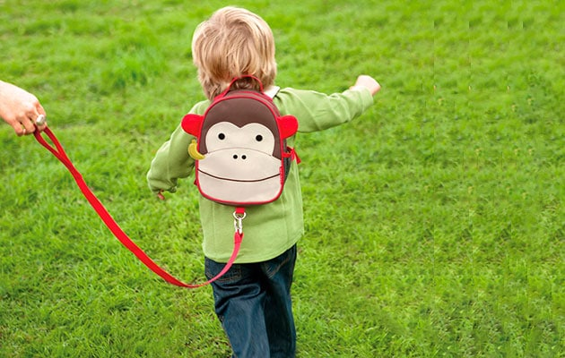 child running on grass attached to backpack safety leash