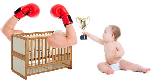 crib with arms held high while baby awards trophy