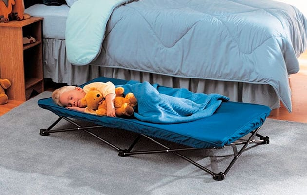 kid sleeping on a portable toddler bed beside an adult bed