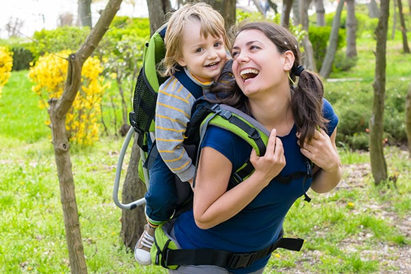 mom carrying a baby inside a backpack carrier