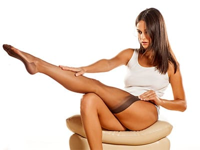 woman pulliong on compression stockings