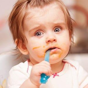 baby girl self feeding with a blue spoon
