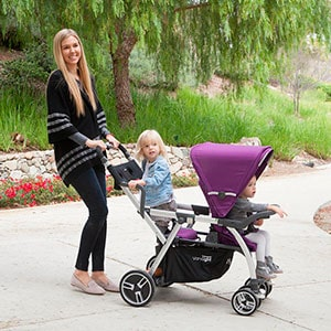 Mom pushing sit and stand stroller on concrete with two kids