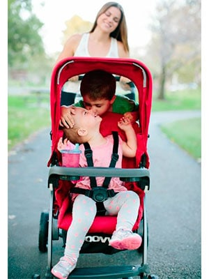 brother kissing his sister while being pushed in a sit and stand stroller