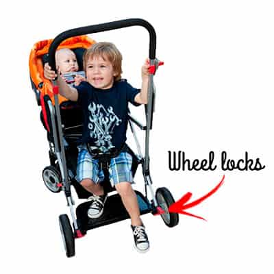 kid sitting ont he back of the joovy caboose with his feet near the wheel locks