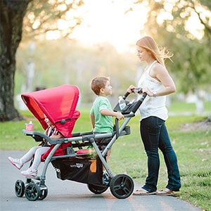 mom walking her two kids through the park pushing a sit and stand stroller