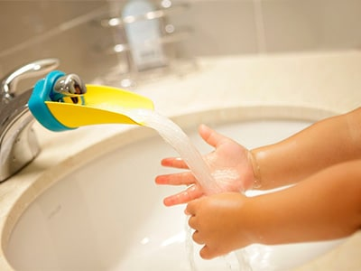 toddler washing his hands qith aqueduck faucet extender