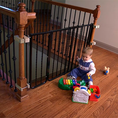 baby gate installed between round newel posts at top of stairs