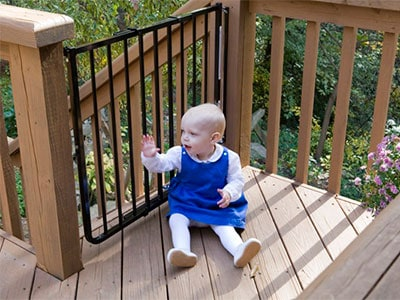 baby playing outside on deack/porch near a baby gate