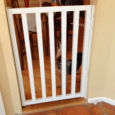 DIY baby gate sitting in narrow door frame