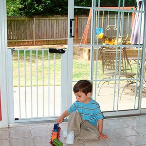 little boy playing in front of sliding glass door with baby gate installed