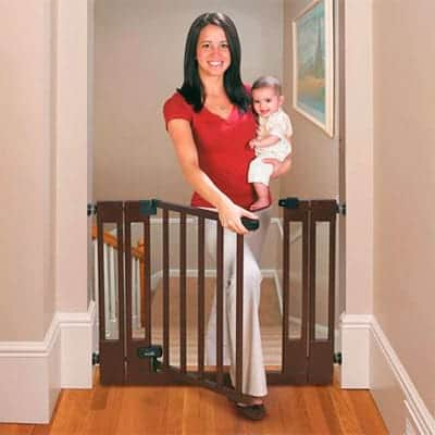 mom walking through summer infant duluxe dark wood baby gate with baby in hand