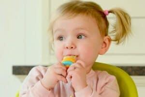baby girl gnawing on kidsme baby food feeder