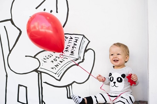 smilling toddler holding balloon