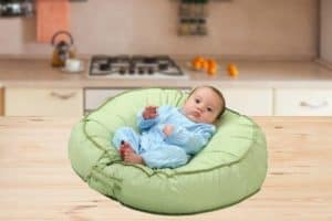 Baby laying on infant lounger in kitchen