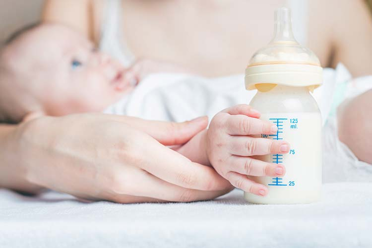 Baby with soy formula in baby bottle