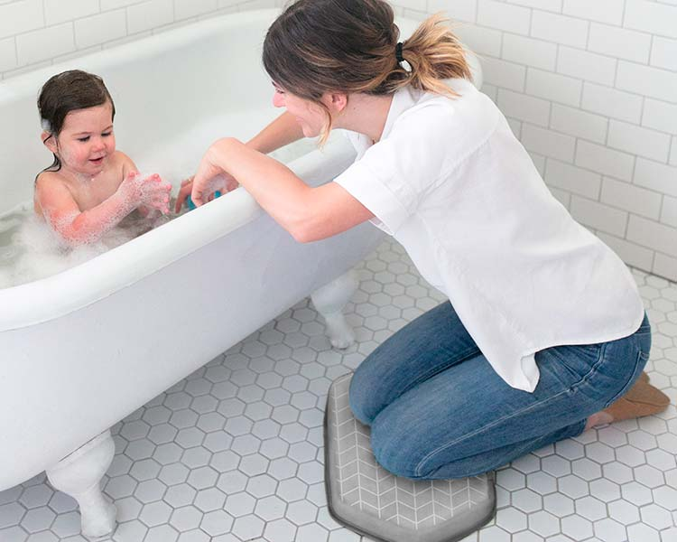 Mom resting knees on bath kneeler while baby is in bath tub