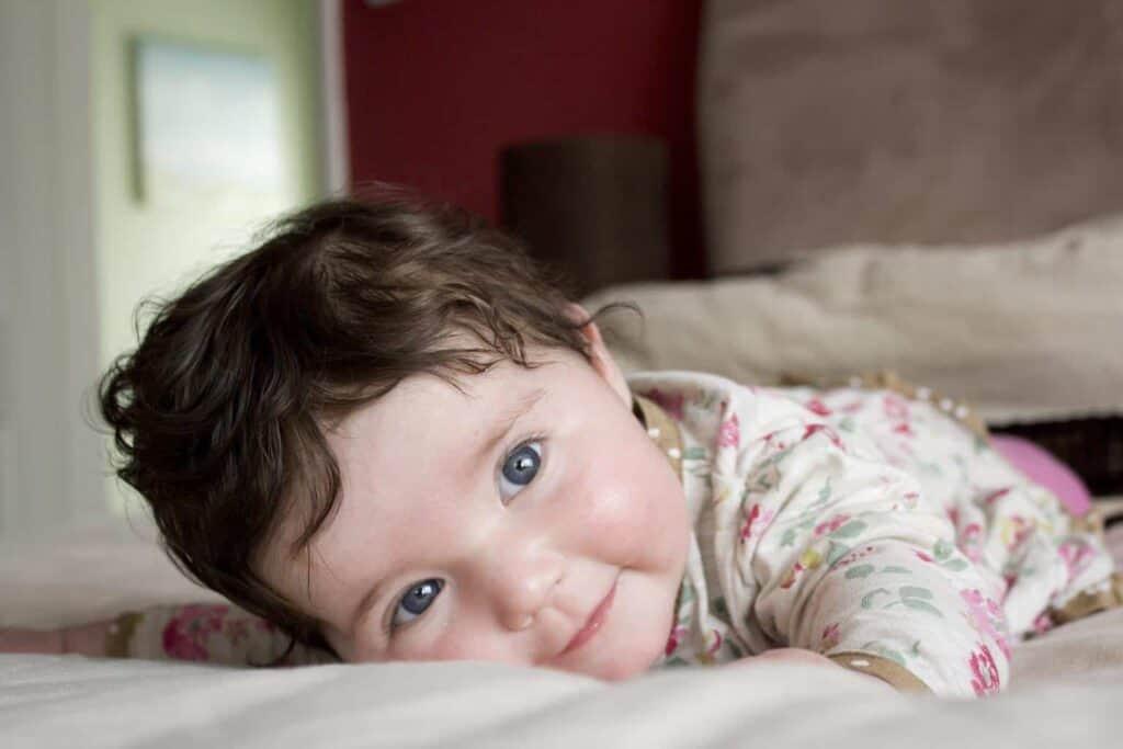 a baby smiles at the camera