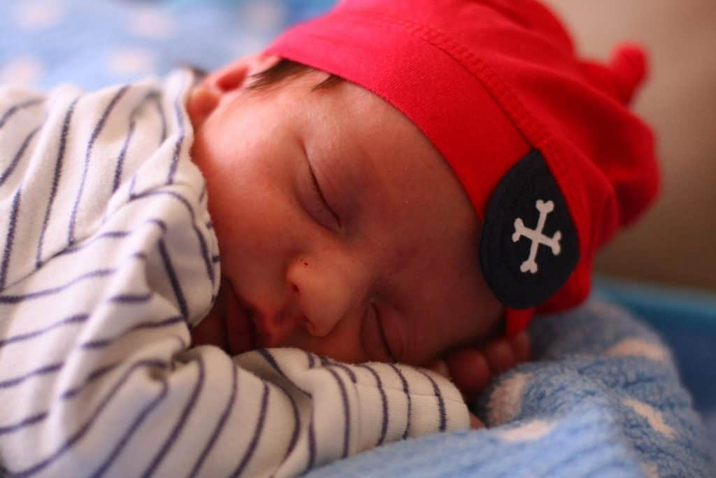 A sleeping baby in a red hat with a pirate patch