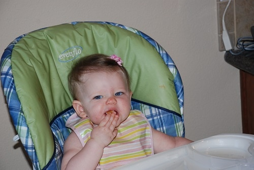 Baby sitting in blue and green highchair