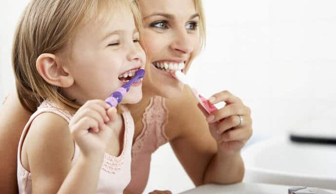 mother and her baby girl brushing their teeth