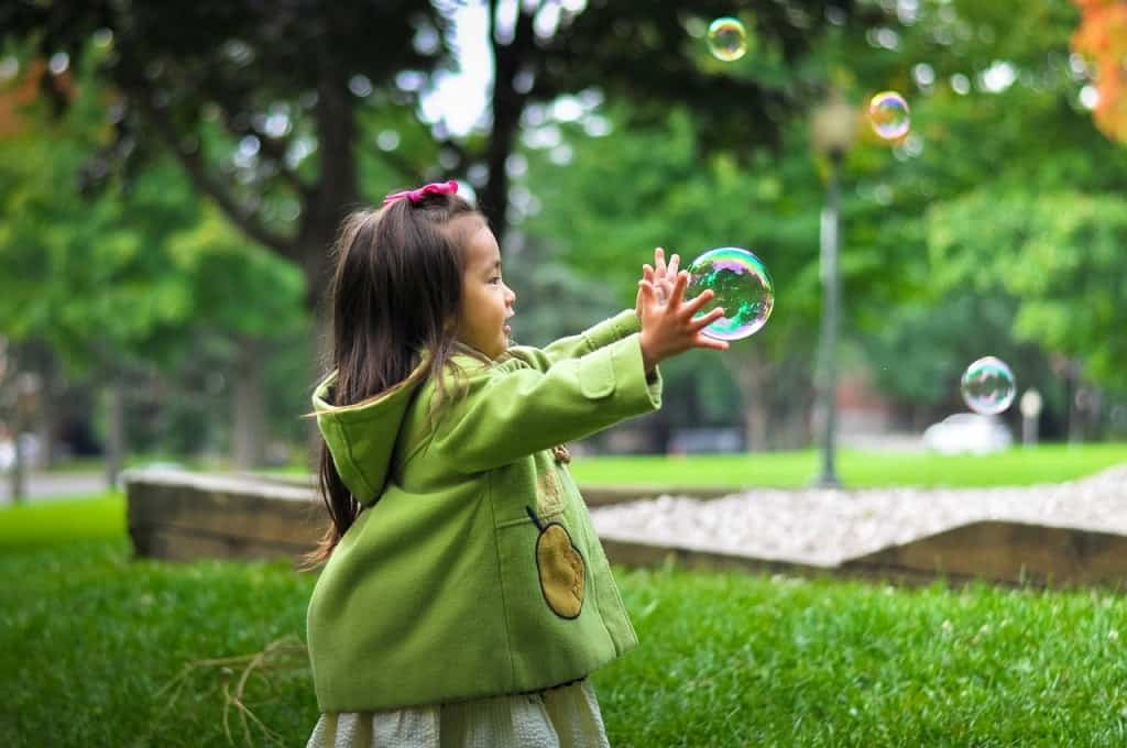 Girl playing on bubbles outdoors