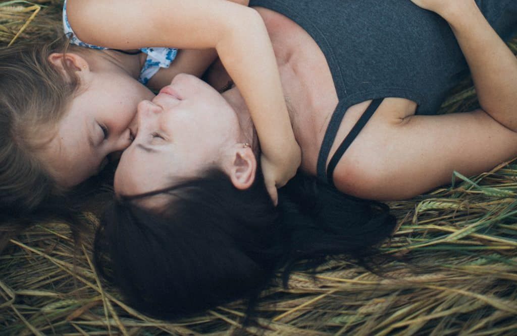 Mother and daughter sleeping in hay