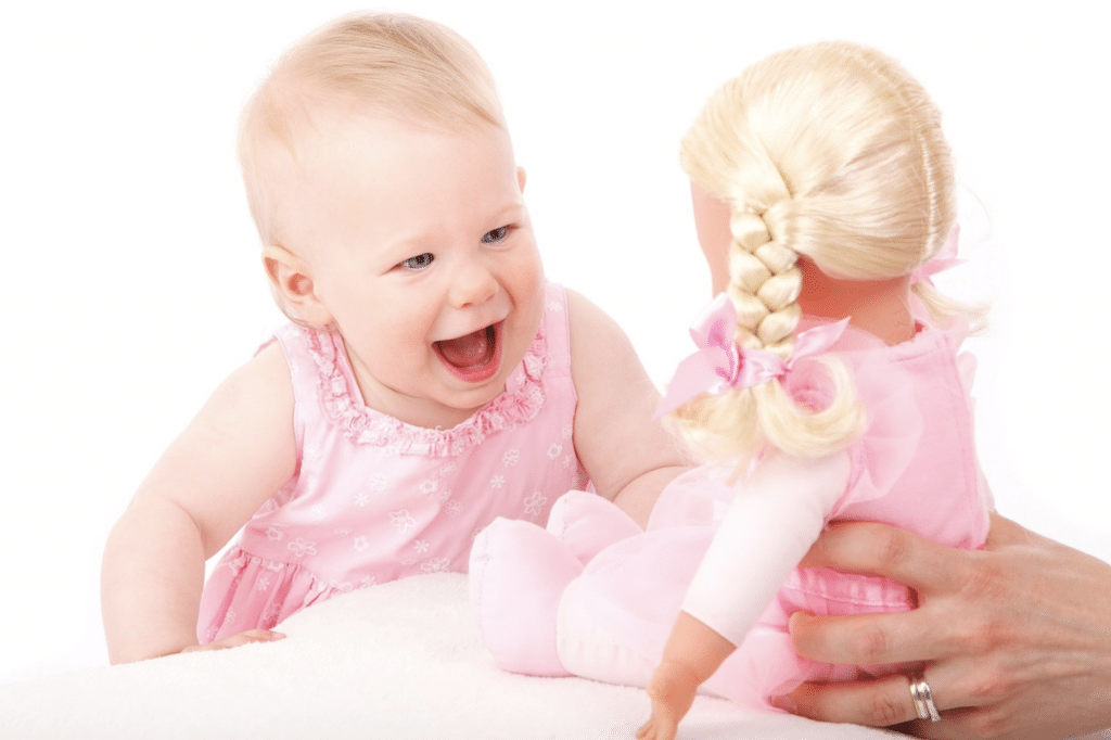 happy baby seeing the doll