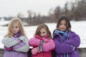 Three girls wearing winter coats