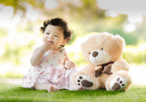 toddler sitting on a grass with brown teddy bear