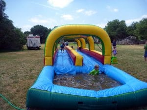 Kids enjoying the best slip and slide in the ground