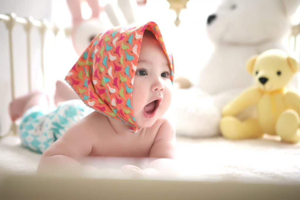 Baby wearing headscarf in bed