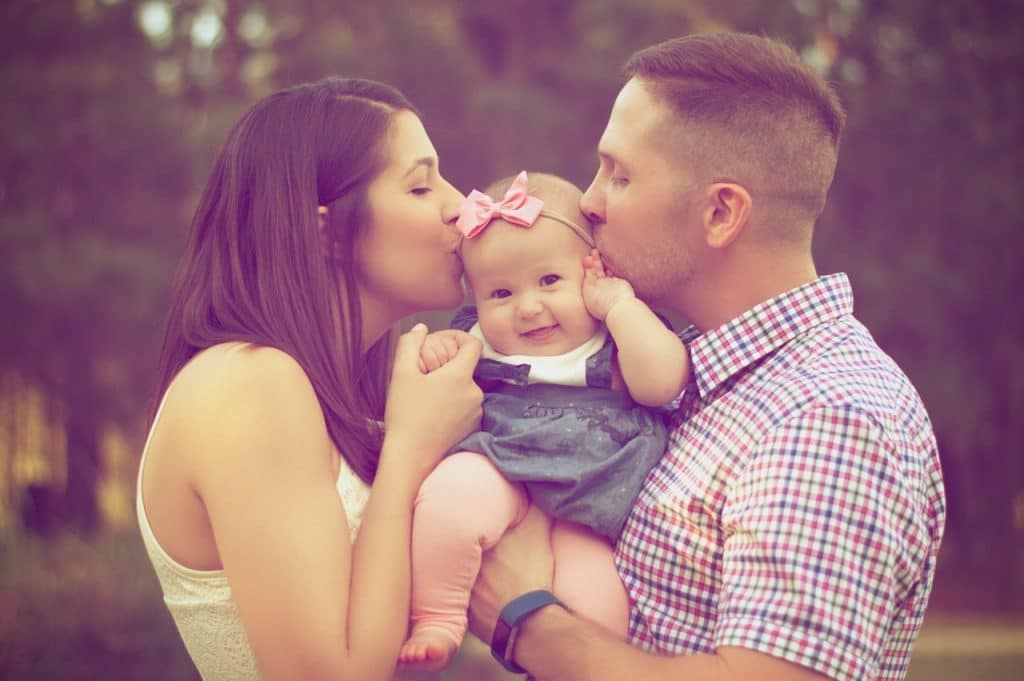 Couple kissing baby while carrying