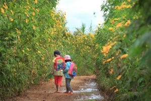 2 Kids walking on a dirt road while carrying the best kids backpacks on their back