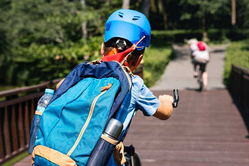 Kid riding a bike is wearing a helmet and the best kids backpacks