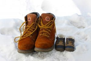 one of the best kids snow boots beside a pair of adult snow boots