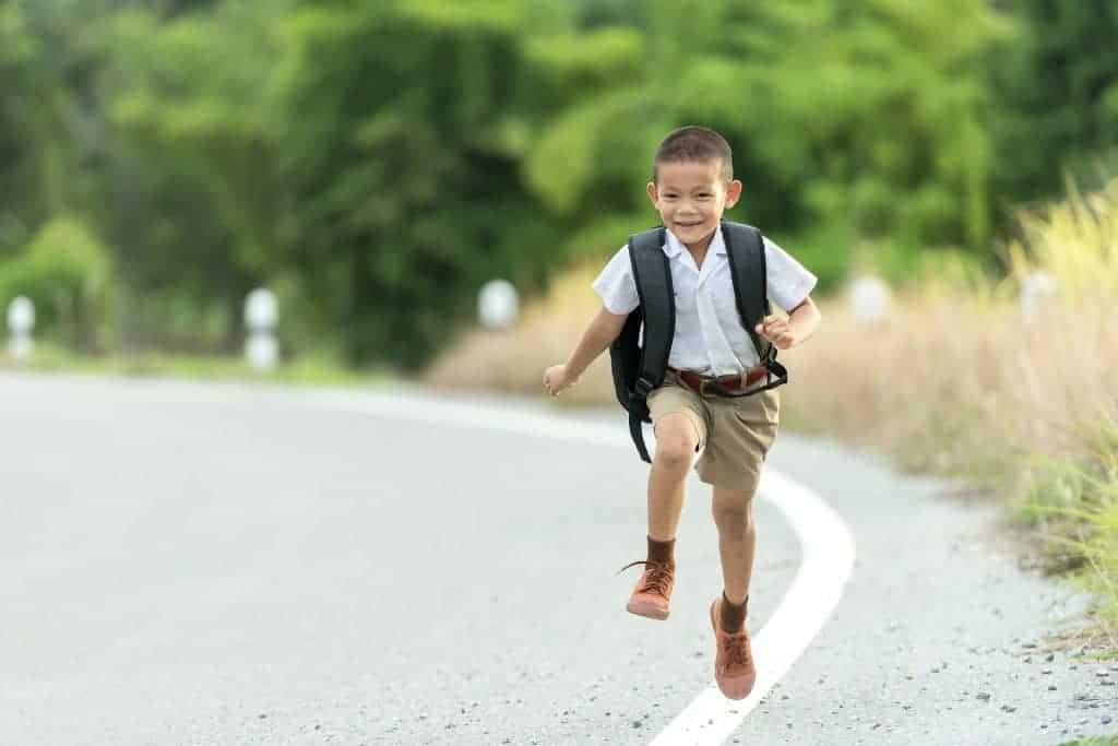 Running Little Boy wearing a school uniform and the best kids backpacks