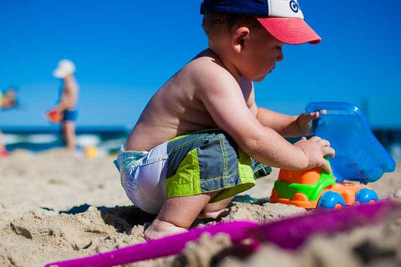 boy playing in the sand with his toy truck
