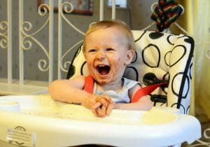 baby with a dirty face is laughing while sitting at the high chair