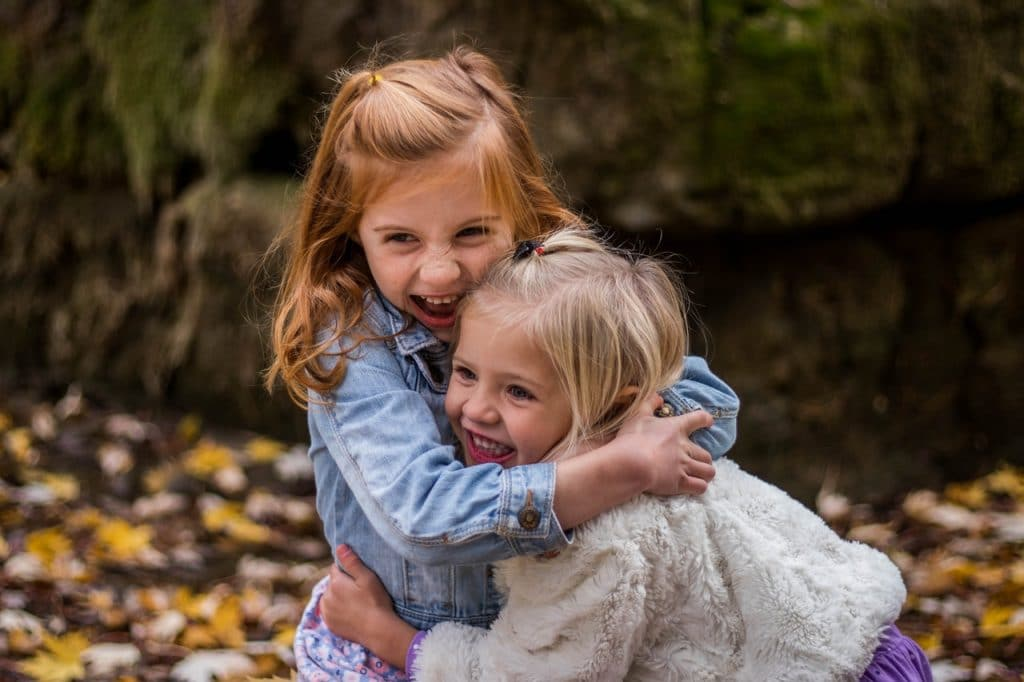 Two little girls hugging each other