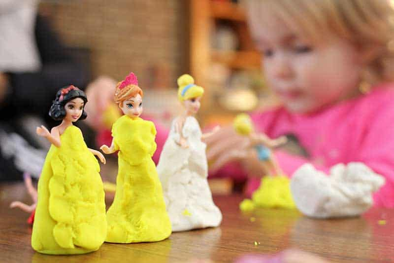 girl playing on the three disney figurine