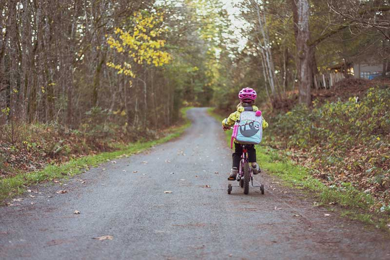 Little girl riding a bike is wearing an helmet and the best kids backpacks