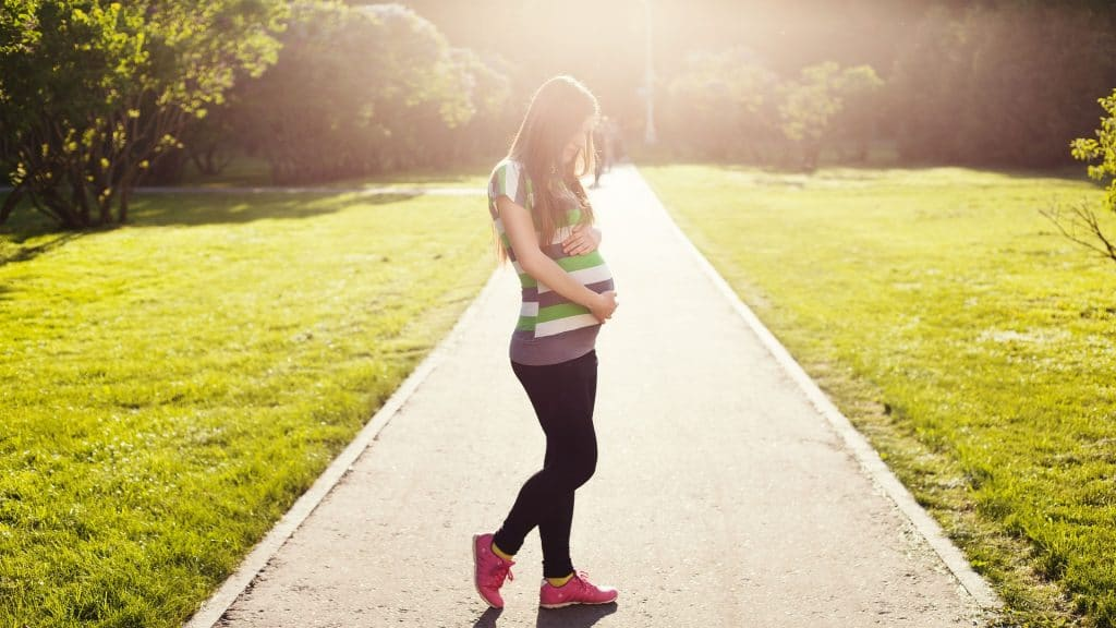 Pregnant women is standing at the park and she is wearing the best maternity leggings