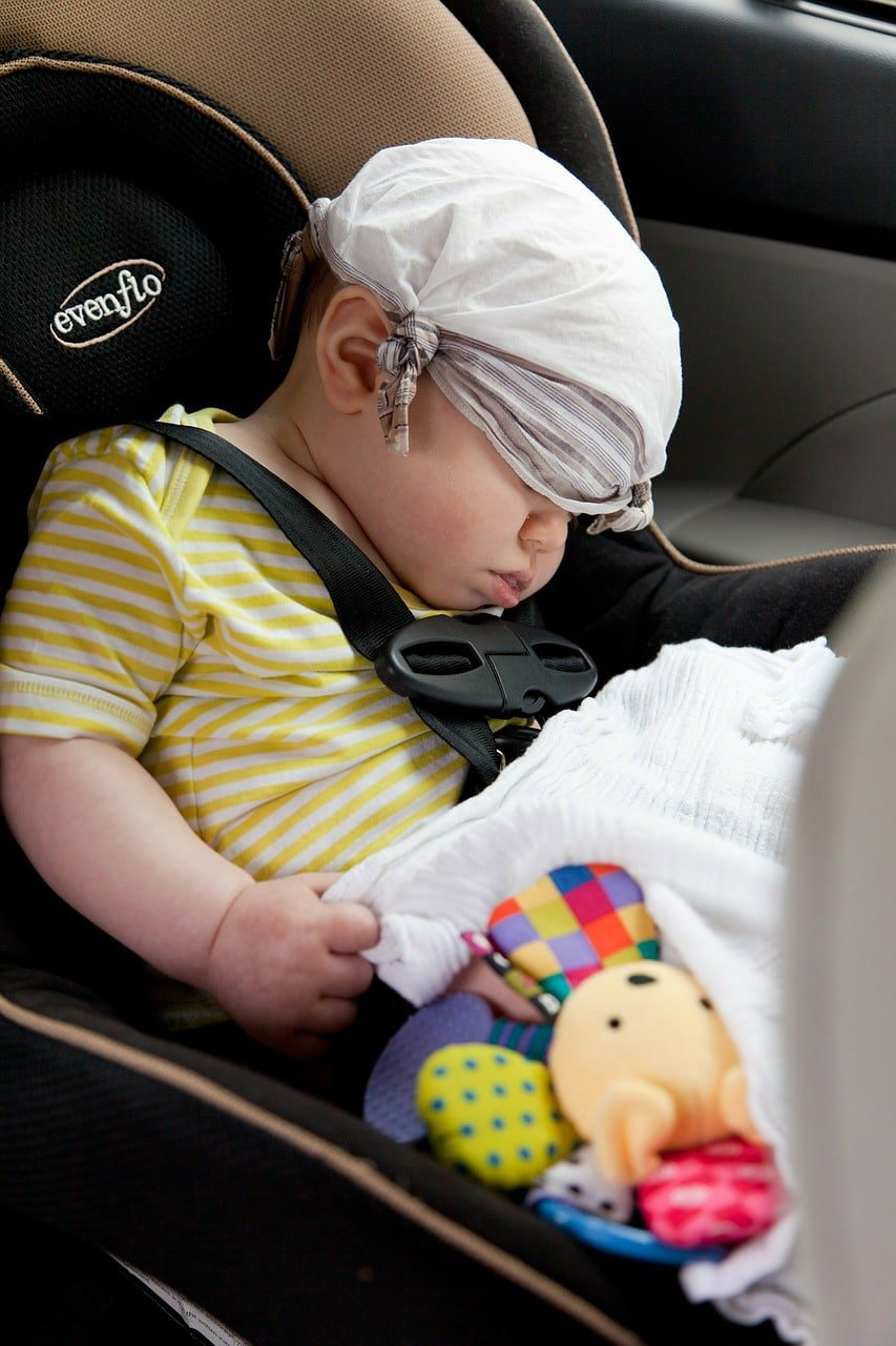 Baby boy is sleeping while seating at the car seat