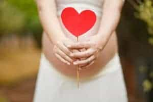 Photo of a pregnant woman holding a red heart